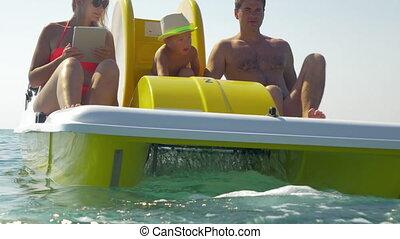 Family of three enjoying water ride on pedal boat - Man,...