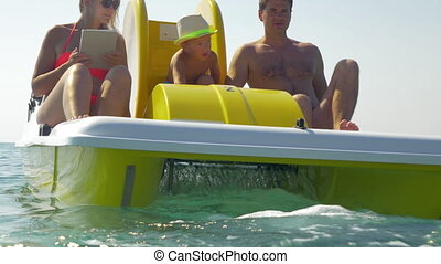 Family of three enjoying water ride on pedal boat - Man,...