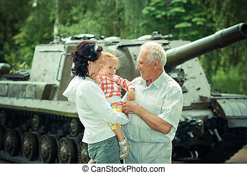 family of three generations having fun on the background of the historic vintage military vehicle. Family portrait of three generations on the background of military equipment
