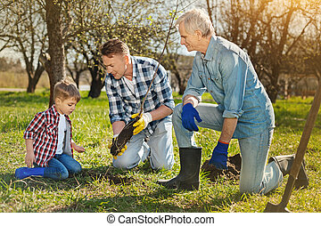 Family of three generations planting the tree in the garden