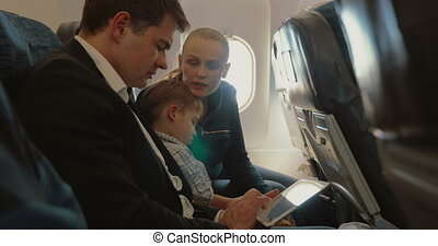 Family of three in plane with smartphone and tablet PC