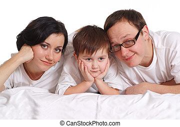 Family of three in white shirts on the bed