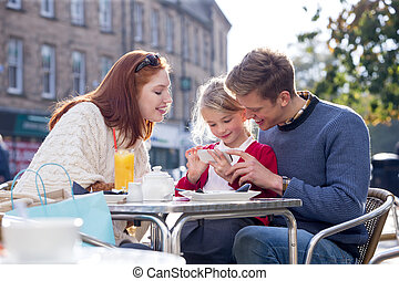 Family of Three Looking at a Smartphone