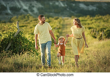 Family of three mom dad and daughter walking in a grape field