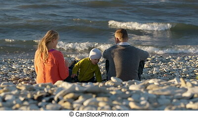 Family of three on pebble beach.
