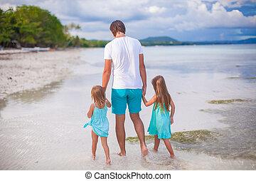 Family of three on tropical white beach