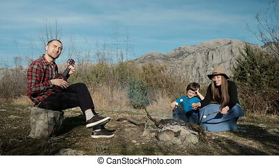 Family of three people is singing songs by the fire and frying a snack.