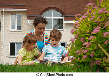 Family of three people on lawn in front of house. Mother with her daughter and son see paper.