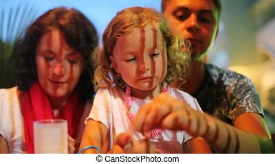 family of three persons eating in night cafe, focus on little girl