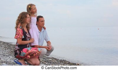 family of three persons sitting on pebble coast and looks at sea