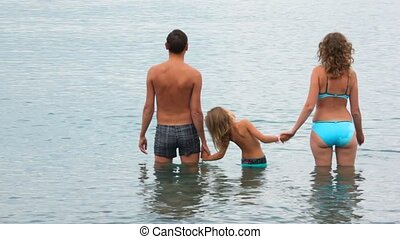 family of three persons standing in water of sea, join hands