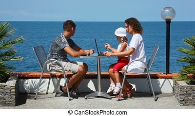 family of three persons with notebook sits at table, sea in background