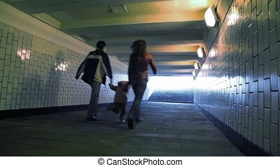 family of three running in underground passage from camera, joined hands