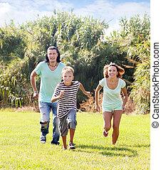 Family of three running on grass