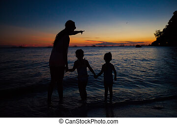 Family of three silhouette in the sunset on Boracay beach