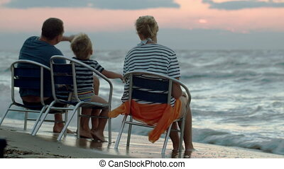 Family of three sitting on chairs by sea at sunset