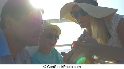 Family of three traveling by sea and using mobile
