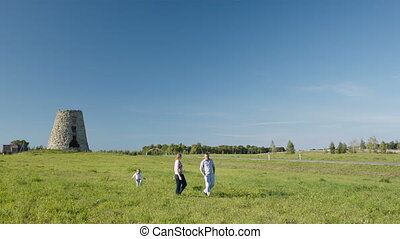 Family of three walking in the countryside.