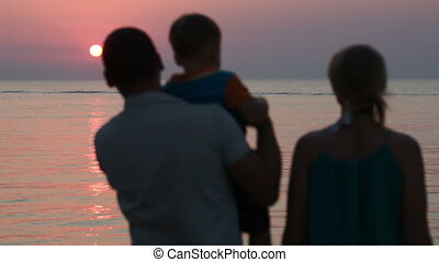 Family of three watching sunset over sea
