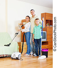family of three with cleaning equipment - ordinary family of...