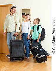Family of three with teenager by the door with bags