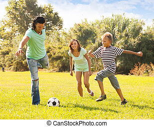 Family of three with teenager playing in soccer