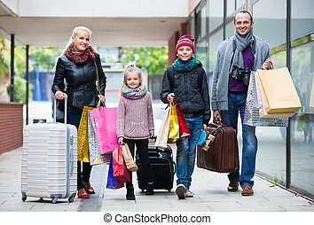 Family of tourists carrying shopping bags - Happy family of ...