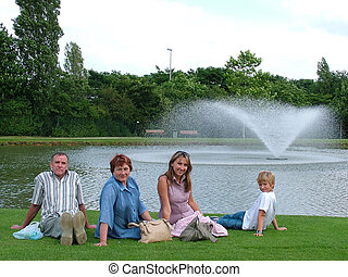 Family on a grass under the blue sky