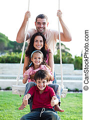 Family on a swing  - Family having fun on a swing