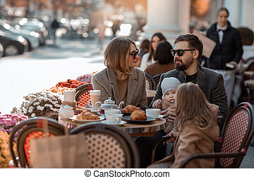 Family on a trip to the European square in a street cafe stopped for a snack