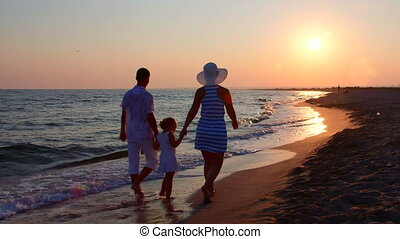 Family on beach getaway walking away holding hands along surf line at sunset