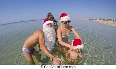 Family on beach vacation having fan taking selfie beside Christmas tree in water