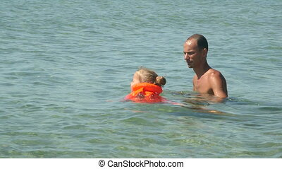 Family on beach vacation teaching little daughter in inflatable vest how to swim