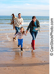 Family on Beach with Seaweed - Young father chasing his...