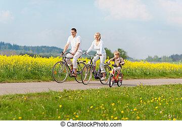 family on bikes - happy family riding bikes in green ...