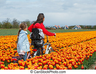 Family on bikes in spring flower fields - Cute young woman...
