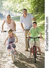 Family on bikes on path smiling