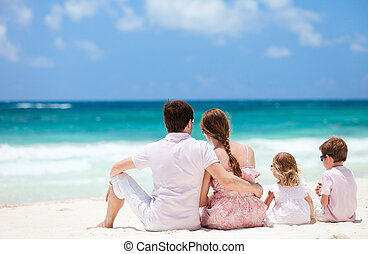 Family on Caribbean vacation - Family of four sitting on...