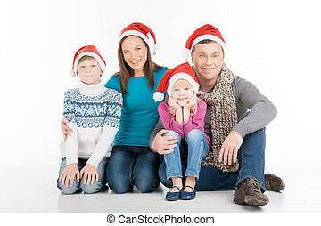 Family on Christmas. Cheerful family in Santa hats looking at camera and smiling while isolated on white