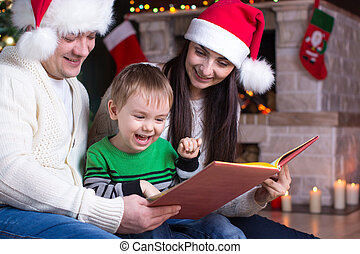 Family on Christmas Eve by the fireplace reading a book to their child