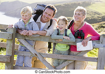 Family on cliffside path leaning on fence and smiling