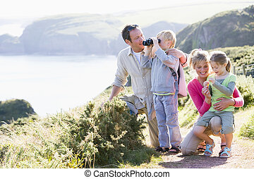 Family on cliffside path using binoculars and smiling