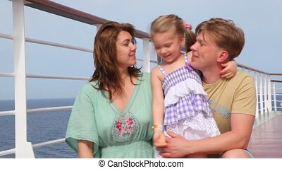 family on cruise liner deck embracing