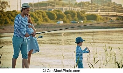 Family on fishing - father fishing - his wife holding a baby - little boy walking on the beach
