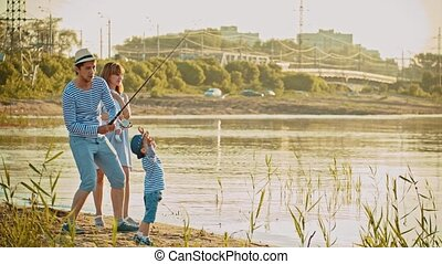 Family on fishing - father holding a fishing rod and showing how to fishing to his son