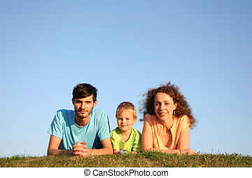 Family on herb under blue sky lie