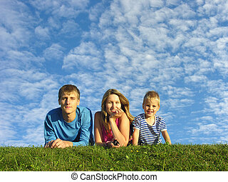 family on herb under blue sky family on herbfield under...