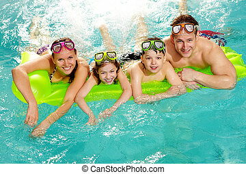 Family on matress - Cheerful family in swimming pool smiling...