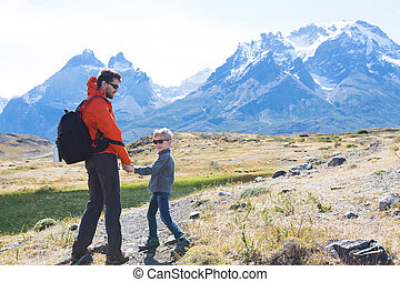 family on patagonia - back view of playful family hiking in...