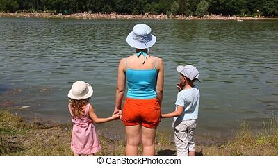 Family on river bank in summer day.